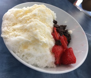 Vanilla snow ice topped with condensed milk and with a side of chocolate chips and strawberries (a few bites taken of course).